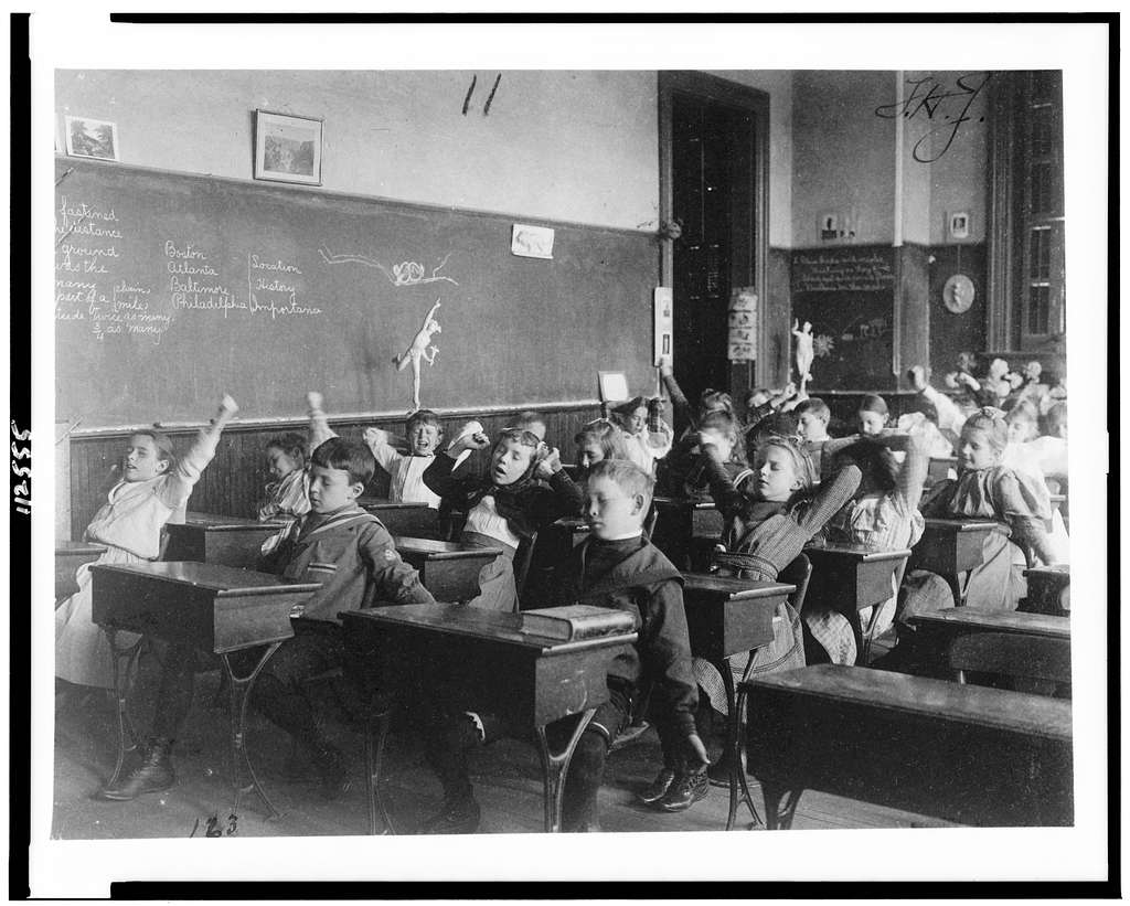 Image used under a Collective Commons License from https://picryl.com/media/children-seated-at-desks-in-washington-dc-classroom-stretching